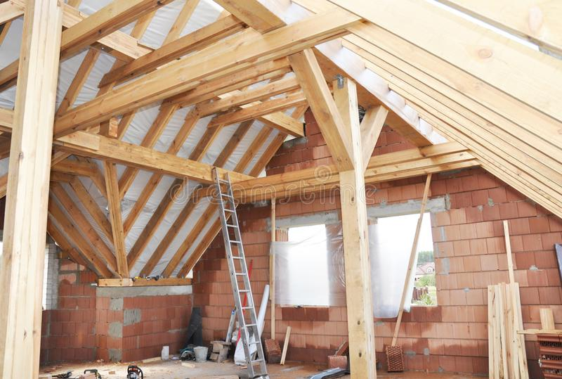 Unfinished House Attic Construction Interior. Building house attic room with roofing wood trusses, frame, wooden beams. stock photos