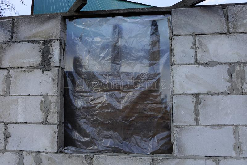 Unfinished house of gray brick and window closed by cellophane royalty free stock image