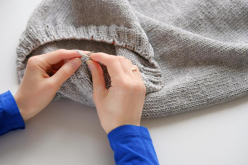Unfinished knitting project in the hands of a young woman on a white background. A girl knits a wool cloth. stock photo