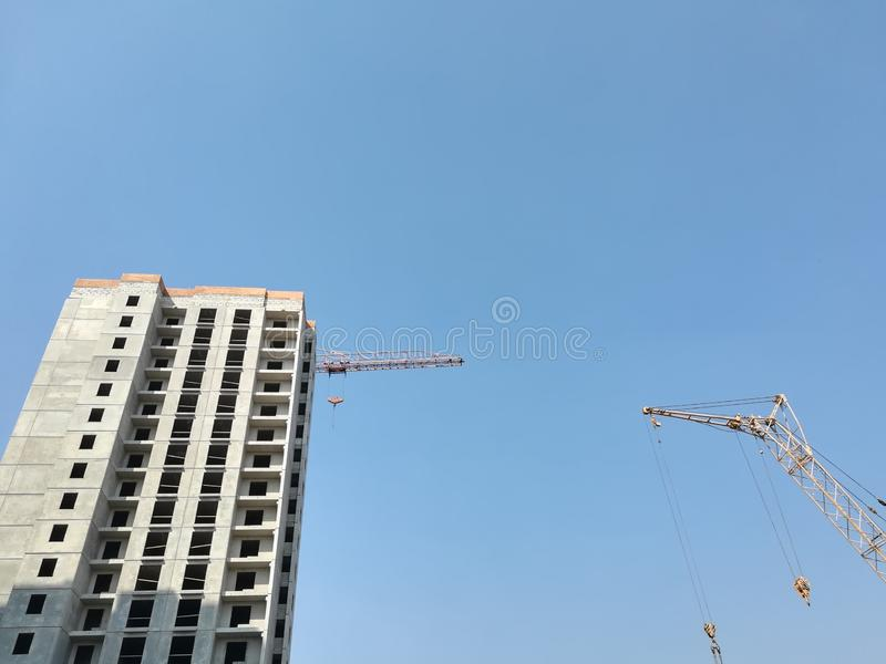 Unfinished multi-storey residential building on a Sunny day against the blue sky. Empty apartment. Bottom-up view. Construction. Crane royalty free stock images