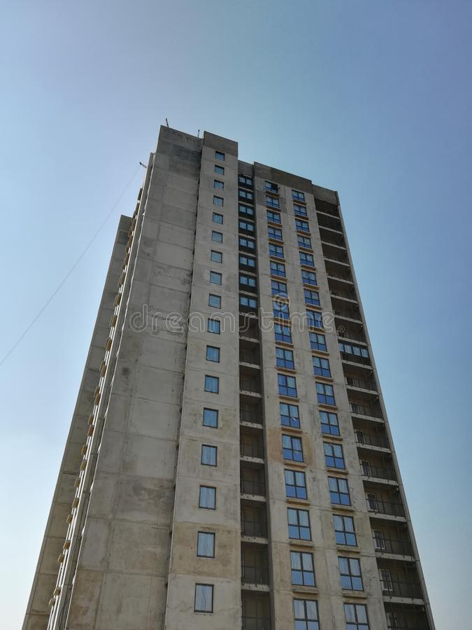 Unfinished multi-storey residential building on a Sunny day. Empty apartment. Bottom-up view. Blue sky.  royalty free stock images