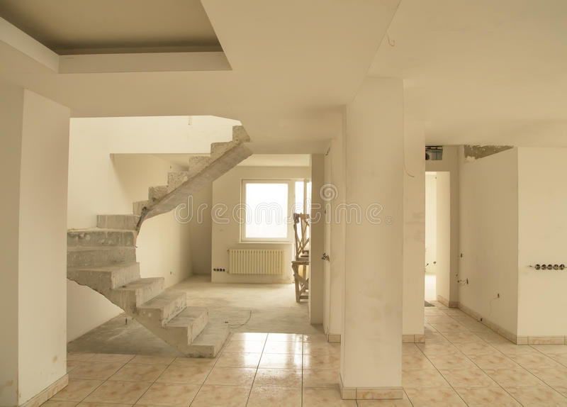 Unfinished office or house rooms. Office or house rooms under construction with ceramic floor tile and white walls and unfinished stairs stock photo