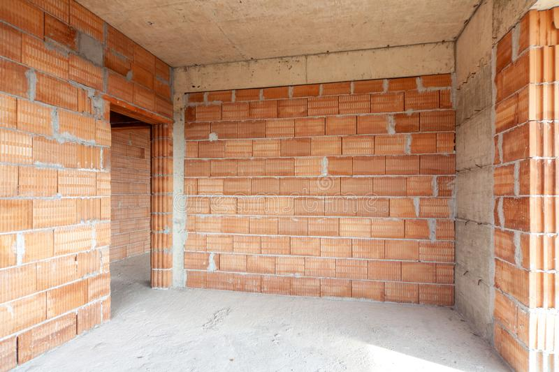 Unfinished room interior of building under construction. Brick red walls. New home. Unfinished room interior of building under construction. Brick red walls royalty free stock images