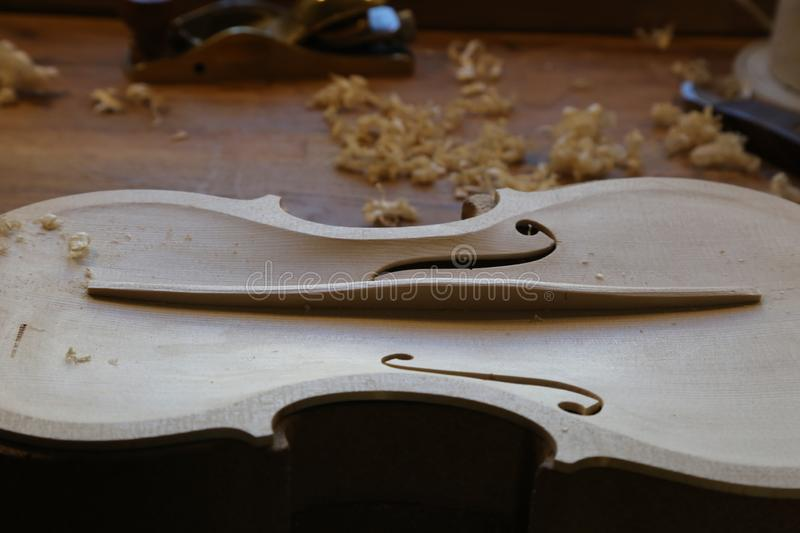 Unfinished violin in luthier, violin maker workshop. Upper face of a violin with the f visible, not lacquered yet, without strings stock photo