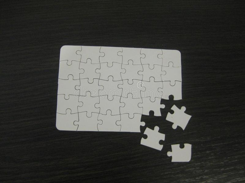 Unfinished white jigsaw puzzle pieces on black background stock photos