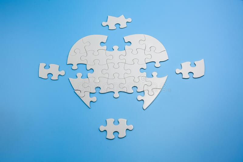 Unfinished white jigsaw puzzle pieces on blue background,  Copy space stock photos