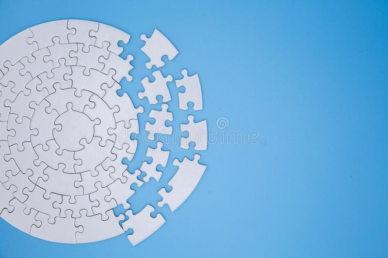 Unfinished white jigsaw puzzle pieces on blue background, The last piece of jigsaw puzzle, Copy space.  stock photo