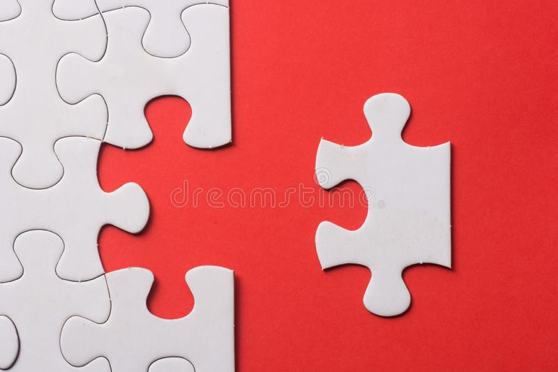 Unfinished white jigsaw puzzle pieces on red background.  stock photo