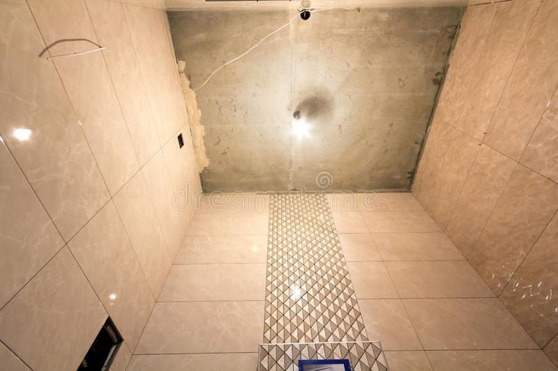 Unfinished work, light beige ceramic tiles installed on walls of bathroom or toilet. Tiles installation, home improvement,. Renovation and construction stock images
