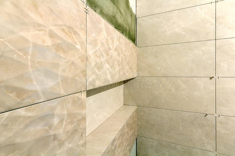 Unfinished work, light beige ceramic tiles installed on walls of bathroom or toilet. Tiles installation, home improvement,. Renovation and construction royalty free stock image