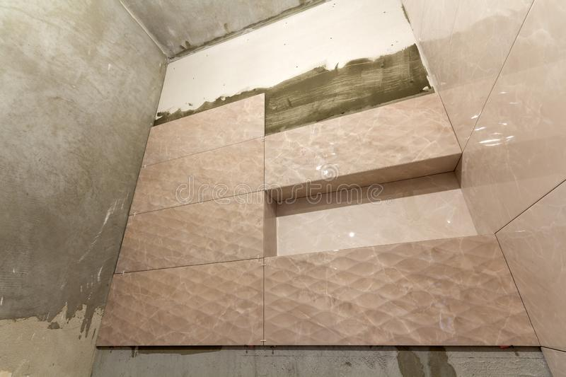 Unfinished work, light beige ceramic tiles installed on walls of bathroom or toilet. Tiles installation, home improvement,. Renovation and construction royalty free stock photography