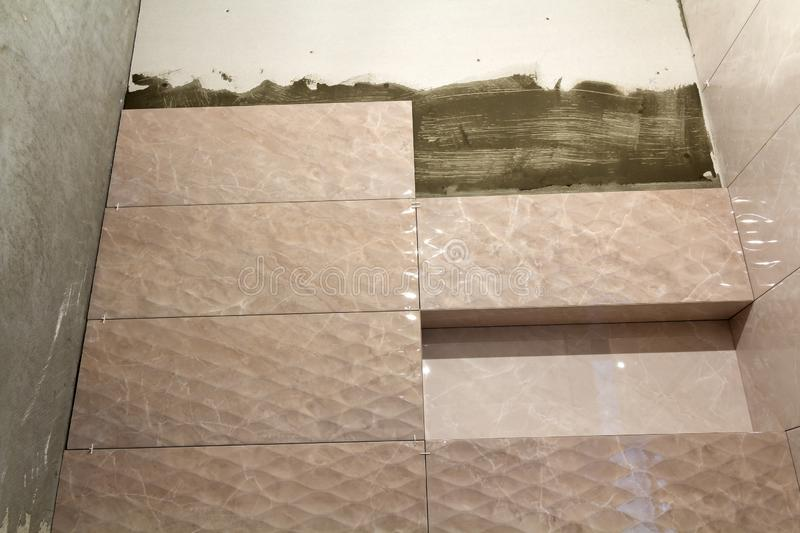 Unfinished work, light beige ceramic tiles installed on walls of bathroom or toilet. Tiles installation, home improvement,. Renovation and construction royalty free stock images