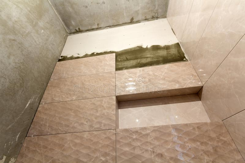 Unfinished work, light beige ceramic tiles installed on walls of bathroom or toilet. Tiles installation, home improvement,. Renovation and construction stock photos