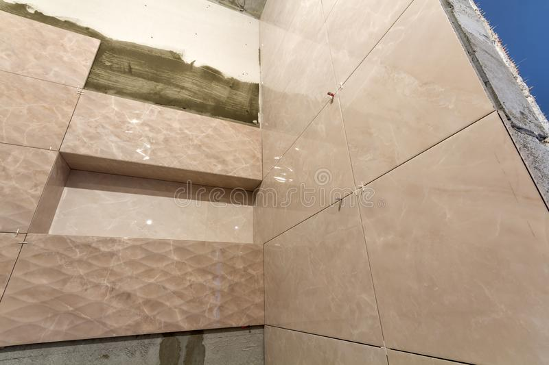 Unfinished work, light beige ceramic tiles installed on walls of bathroom or toilet. Tiles installation, home improvement,. Renovation and construction stock photography