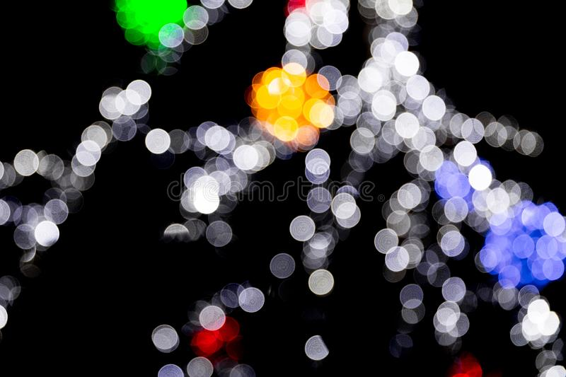 Unfocused abstract colourful bokeh with red, green, orange and blue lamp on black background. defocused and blurred many round. Light stock photo