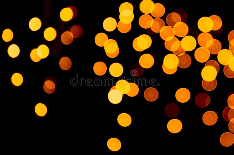 Unfocused abstract gold bokeh on black background. defocused and blurred many round light.  royalty free stock image