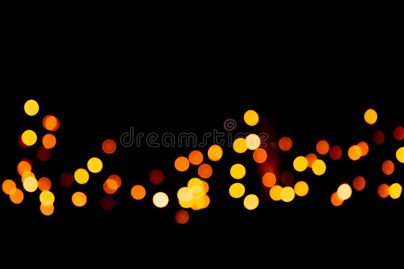 Unfocused abstract gold bokeh on black background. defocused and blurred many round light.  stock photo