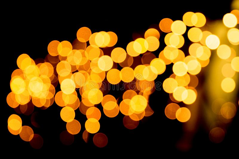 Unfocused abstract gold bokeh on black background. defocused and blurred many round light.  royalty free stock photography