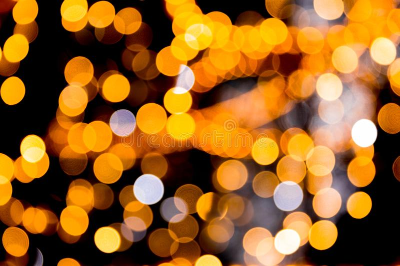 Unfocused abstract orange bokeh on black background. defocused and blurred many round light.  royalty free stock image