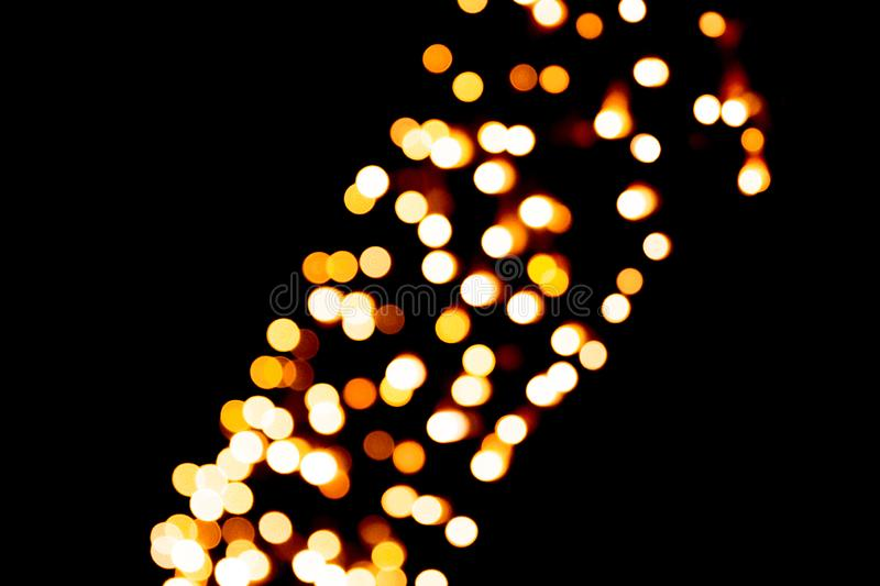 Unfocused abstract orange bokeh on black background. defocused and blurred many round light.  stock photography