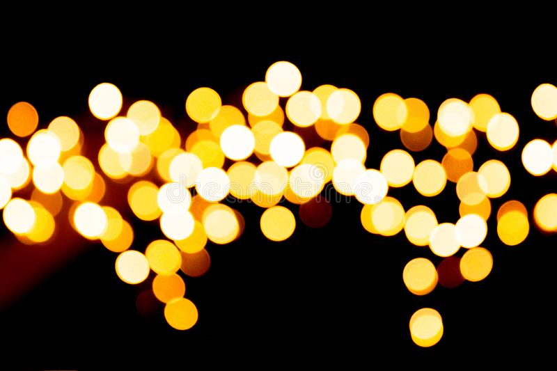 Unfocused abstract orange bokeh on black background. defocused and blurred many round light.  stock image