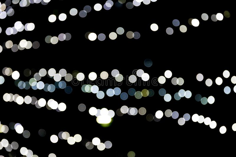 Unfocused abstract white bokeh on black background. defocused and blurred many round light.  royalty free illustration