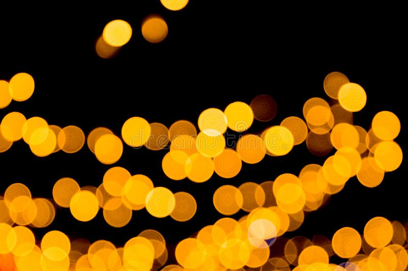 Unfocused abstract yellow bokeh on black background. defocused and blurred many round light.  stock images