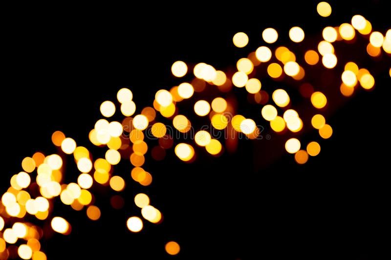 Unfocused abstract yellow bokeh on black background. defocused and blurred many round light.  royalty free stock photo
