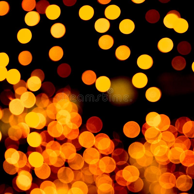 Unfocused abstract yellow bokeh on black background. defocused and blurred many round light.  royalty free stock photography