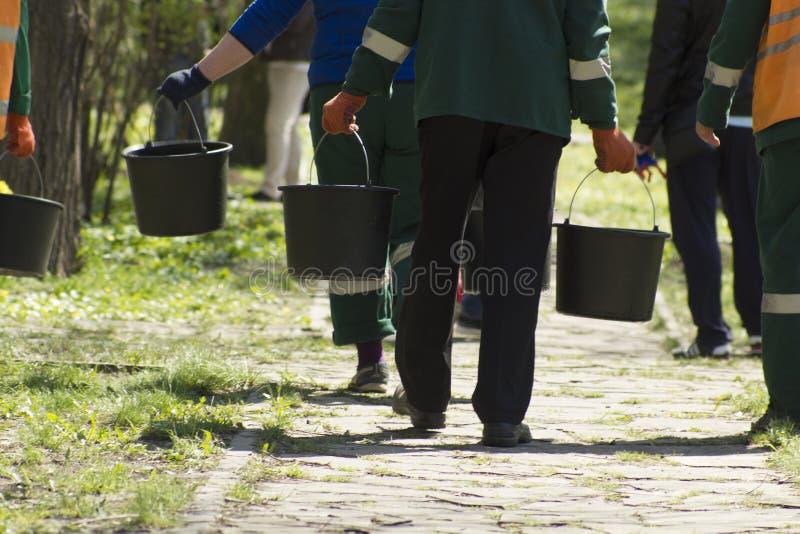 Unfocused arbeta i trädgården servicearbetare som går i avlägset med hinkar med vatten till att bevattna vårjordning och träd på  royaltyfria bilder