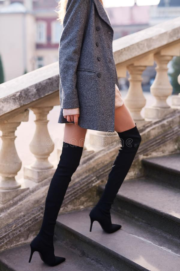 Beautiful fashionable woman in gray coat and black knee high heel boots walking and posing outdoors stock photography