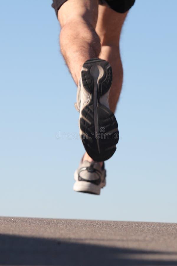 Unfocused sportsman legs running on the asphalt royalty free stock photo