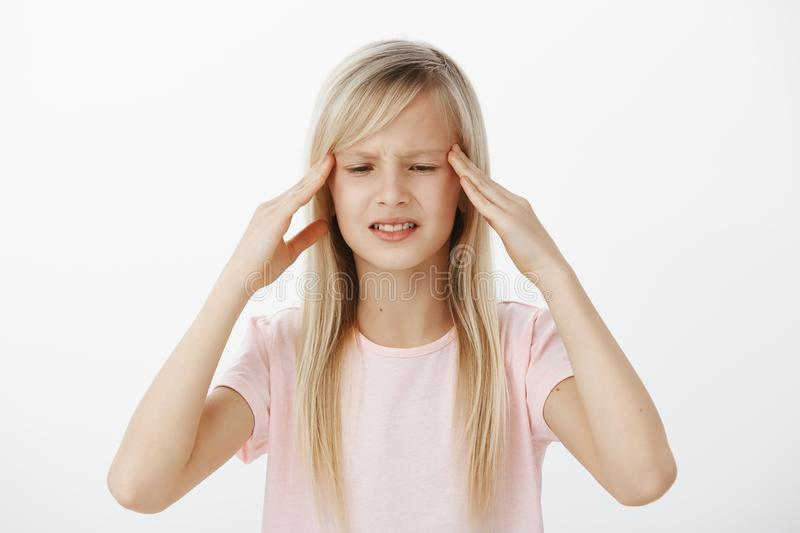 Unfocused worried kid cannot think clearly and hold information in mind. Concerned confused young girl with blond hair royalty free stock photography