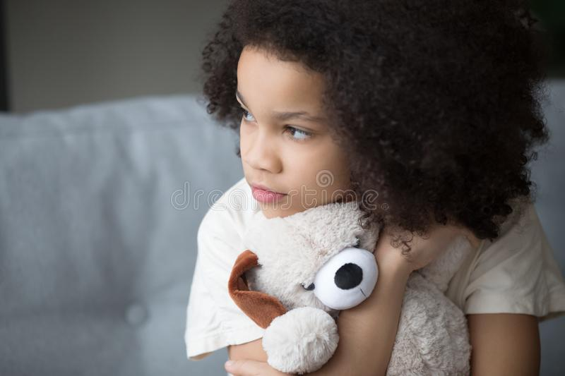 Unfortunate stray biracial kid girl embrace stuffed toy looking aside. Close up upset stray biracial kid girl sitting on sofa cuddle stuffed toy dog looks aside royalty free stock photography