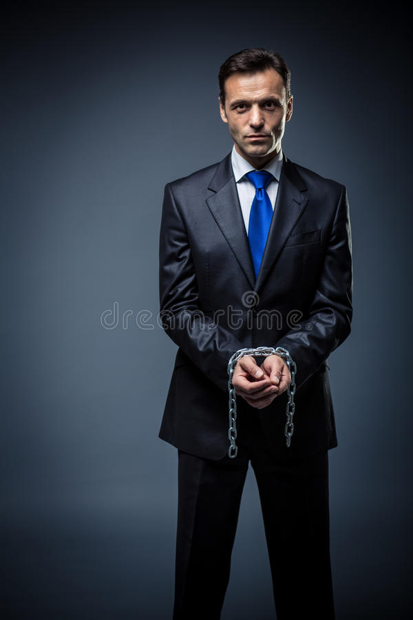 Unfreedom. Business man in a suit with his hands tied stock image