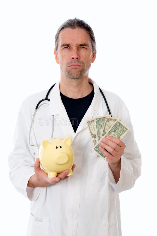 Unfriendly doctor with piggy bank. In white lab coat royalty free stock image