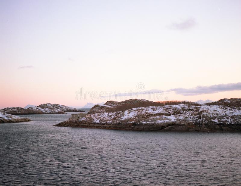 Unfrozen lake in winter and snow islands royalty free stock photos