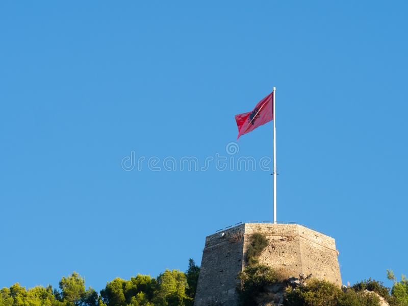 Unfurled Albanian Flag Flying at Berati Castle or Kala Citadel. Unfurled Albanian flag with black double-headed eagle on a red background, flying at Berati stock photo