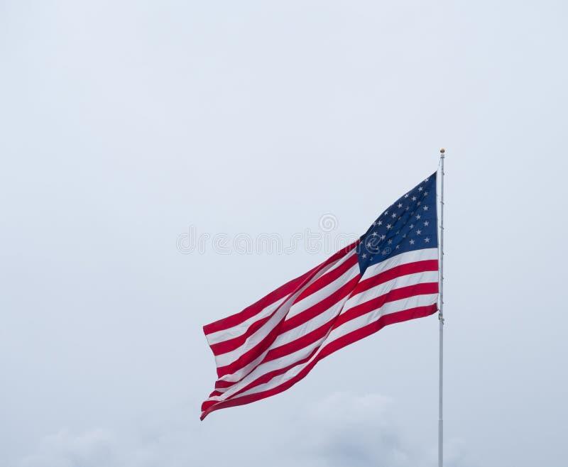 Unfurled flaga amerykańska przeciw Ponuremu niebu obraz stock