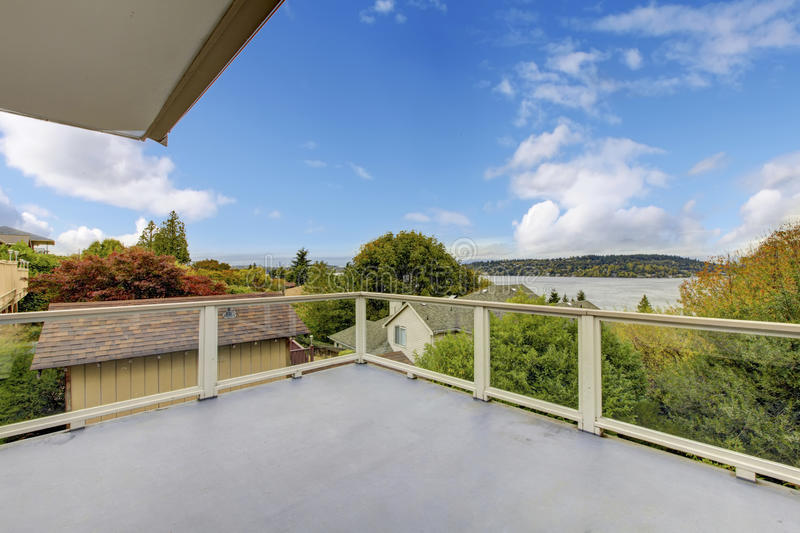 Unfurnished and empty balcony with perfect water view. Unfurnished and empty balcony with glass railings and perfect water view royalty free stock photo