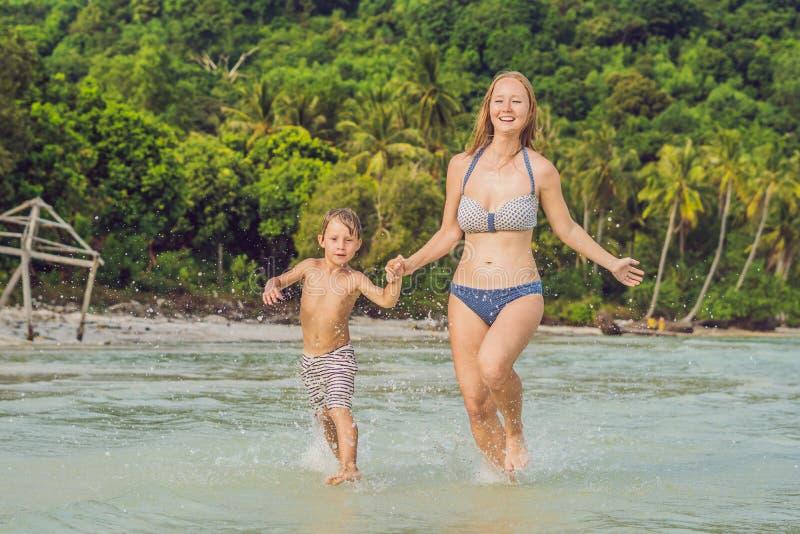 Ung älska moder och hennes liten son som spelar på stranden fotografering för bildbyråer