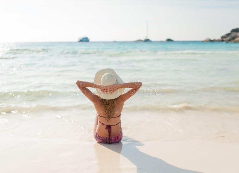 Ung älskvärd flicka som sitter med att koppla av och lycka på stranden royaltyfria bilder