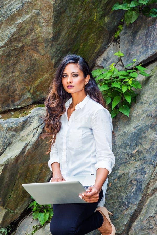 Ung östlig indisk amerikansk kvinna med långt hår som arbetar på bärbar datordatoren som är utomhus- i New York royaltyfria bilder