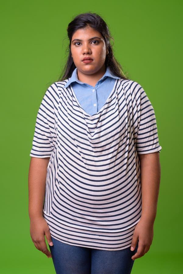 Ung överviktig härlig indisk affärskvinna mot grön bakgrund arkivfoto