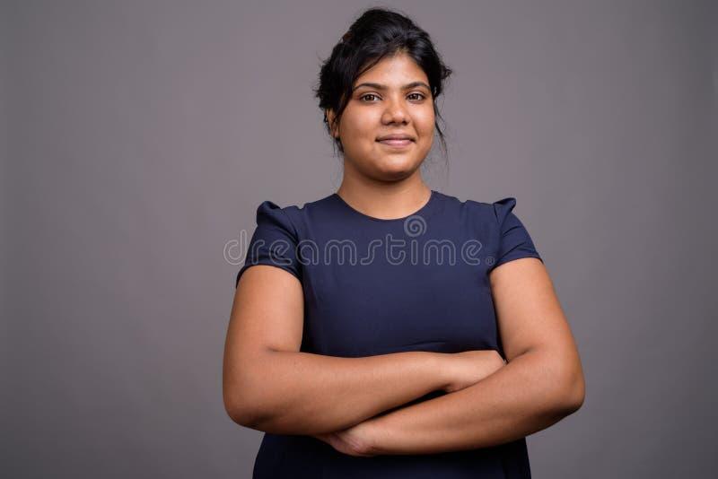 Ung överviktig härlig indisk kvinna mot grå bakgrund royaltyfria bilder
