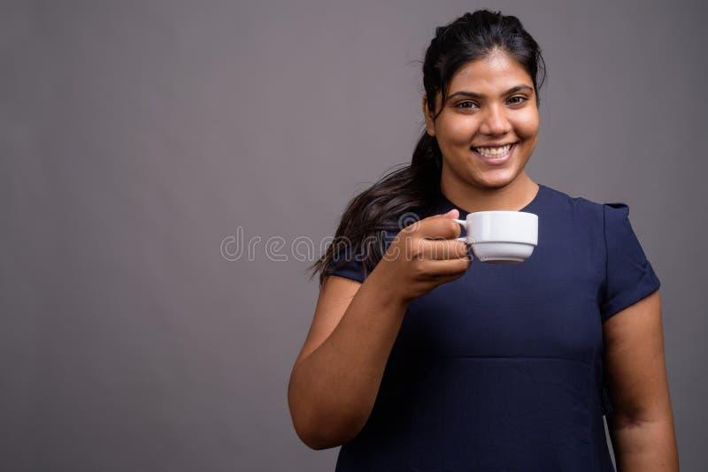 Ung överviktig härlig indisk kvinna mot grå bakgrund royaltyfri bild