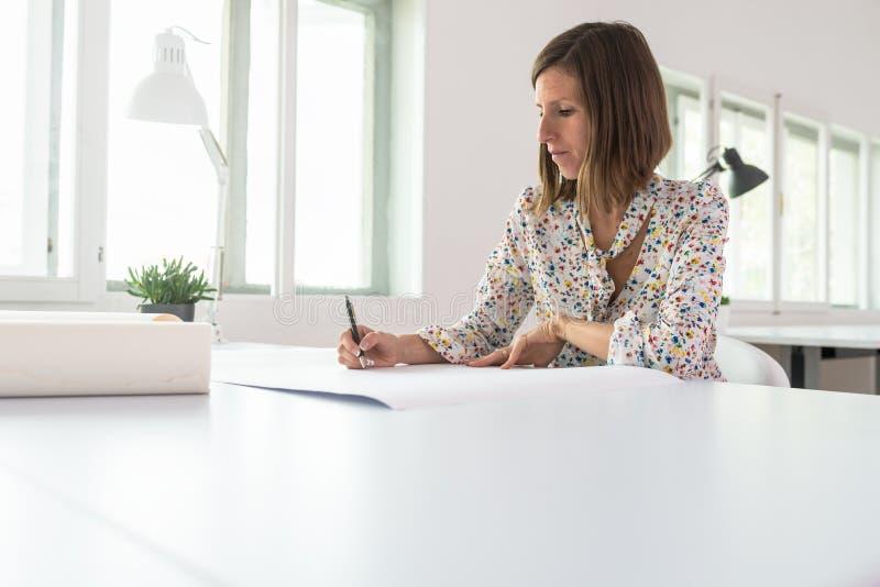 Ung affärskvinna eller formgivare som sitter på hennes kontorsskrivbord som arbetar på ett projekt royaltyfria foton
