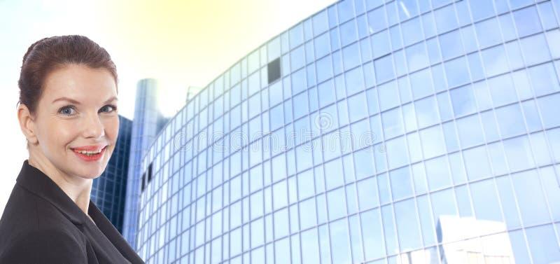 Ung affärskvinna framme av suddig kontorsbyggnadbakgrund royaltyfria foton