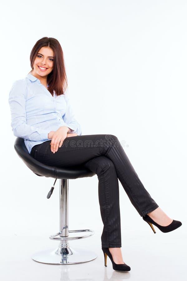 Ung affärskvinna i blått skjortasammanträde på den moderna stolen mot vit royaltyfri bild