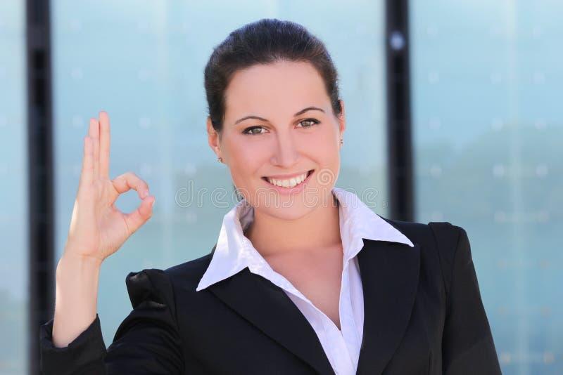 Ung affärskvinna i den svarta dräkten som ok visar royaltyfria bilder